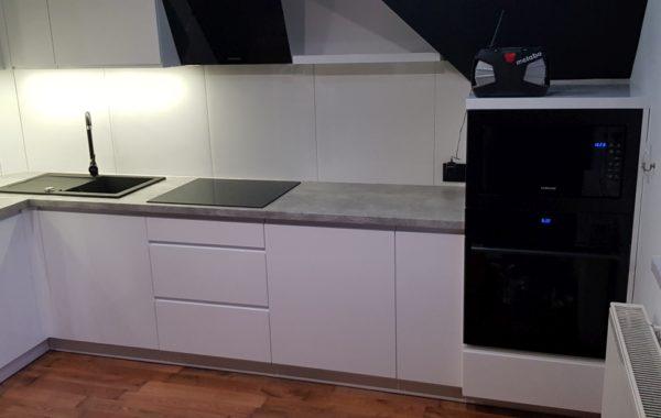 Białe meble kuchenne z grafitowym blatem